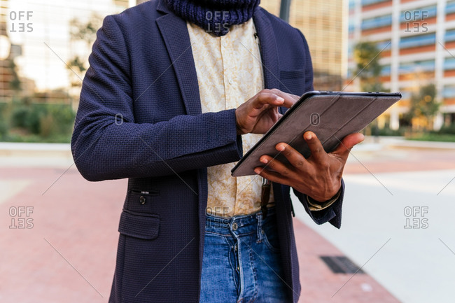Cropped unrecognizable busy African American male freelancer standing in the street browsing on tablet while working remotely on project