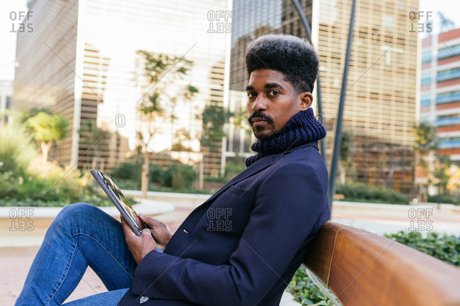 Side view of busy African American male freelancer sitting on bench in street and browsing tablet while working remotely on project