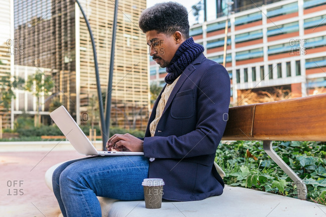 Side view of focused African American male entrepreneur sitting on a bench on the street while working on laptop working on project