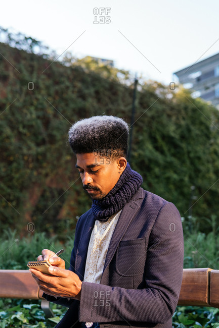Serious African American male entrepreneur sitting on bench in urban park and writing plans in notebook