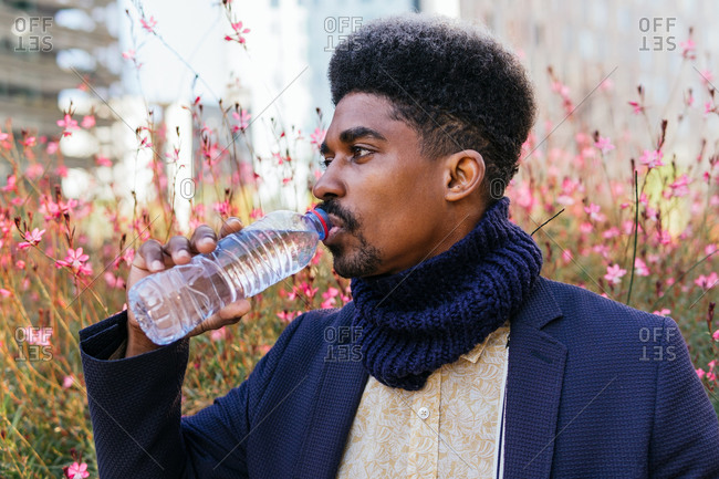 Calm African American male standing in city street and enjoying fresh clear water from plastic bottle while looking away