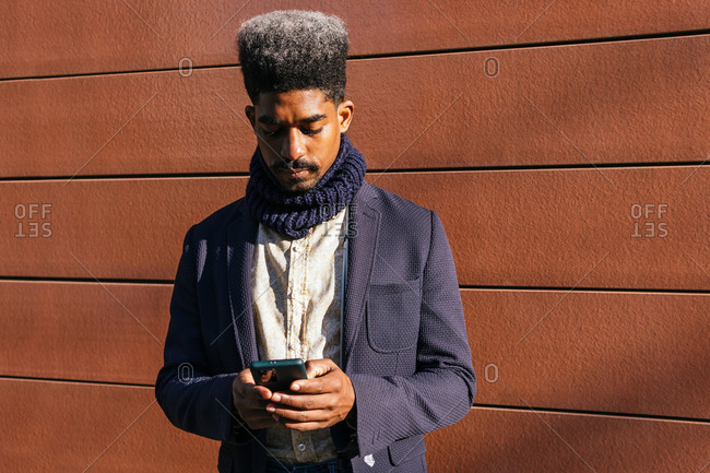 Focused African American male entrepreneur in stylish outfit standing near urban building and reading messages on mobile phone while working remotely in city