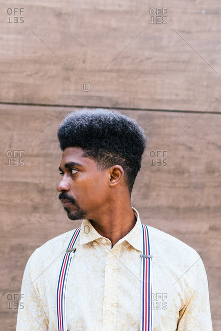Tranquil serious stylish African American male with curly hair wearing suspenders standing on concrete wall of building and looking away while dreaming
