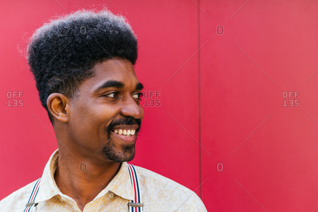 Tranquil cheerful African American male with curly hair standing on red wall of building and looking away while dreaming