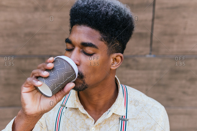 Delighted black male drinking coffee from disposable cup of takeaway with eyes closed