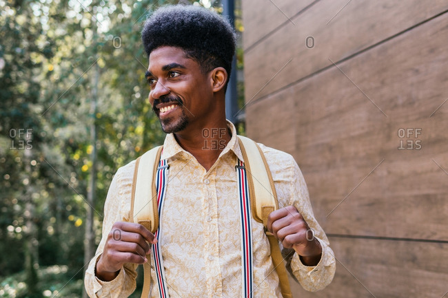 Cheerful adult bearded African American male with afro hairstyle dressed in stylish shirt and suspenders carrying backpack and looking away while standing near building and green trees in forest