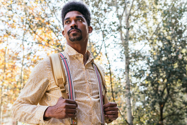 Cheerful adult bearded African American male with afro hairstyle dressed in stylish shirt and suspenders carrying backpack and looking away while standing near green trees in forest
