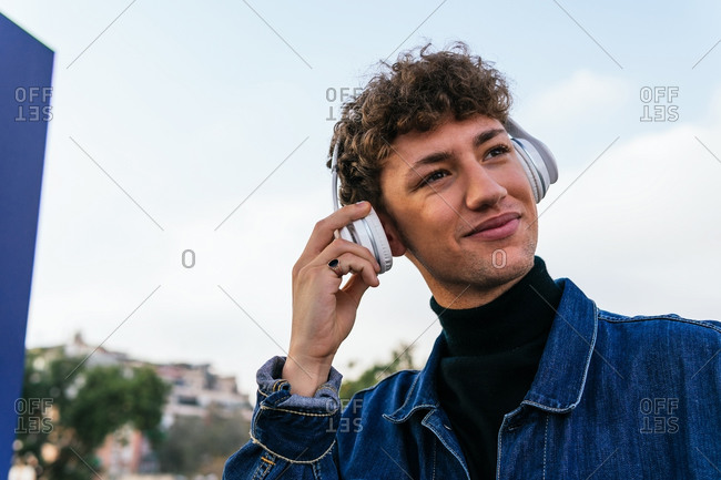 Delighted young male with curly hair and in wireless headphones enjoying music in city and looking away