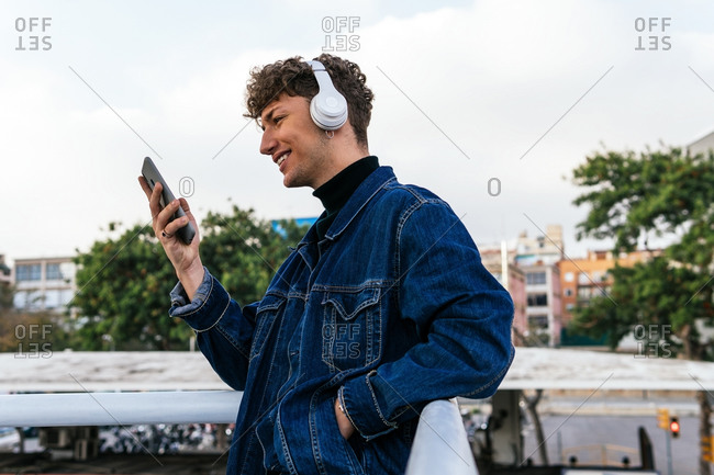 Side view of positive young male listening to music in wireless headphones browsing on smartphone while enjoying weekend in street