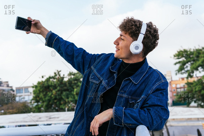 Positive young male listening to music in wireless headphones and taking self portrait on smartphone while enjoying weekend in street