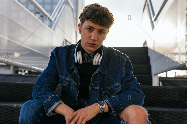 Young male with curly hair wearing denim clothes with wireless headphones around the neck sitting in stairways in city looking at camera