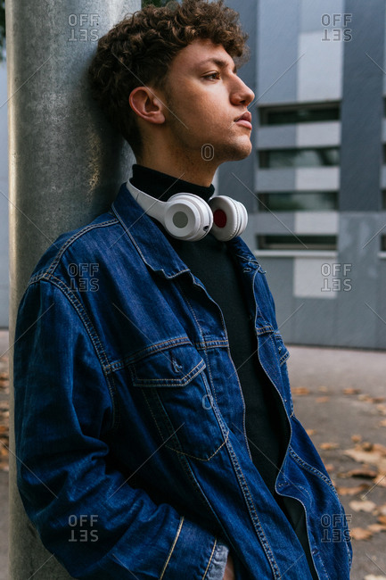 Thoughtful young male with curly hair wearing denim clothes with wireless headphones around the neck standing in city looking away