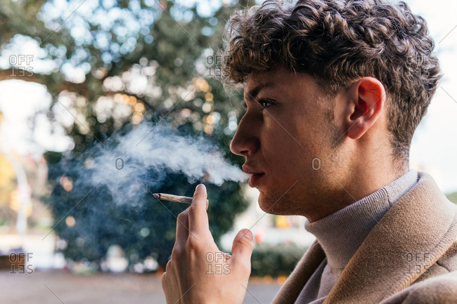 Side view of serious male in stylish outfit standing in street and smoking cigarette while exhaling fume and looking away