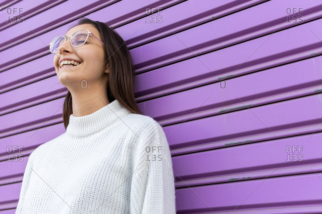 Positive female millennial wearing trendy clothes standing on purple wall on the street enjoying weekend with eyes closed