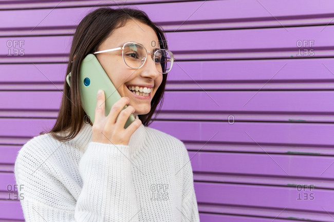 Delighted female millennial standing near purple wall and speaking on smartphone while smiling and looking away