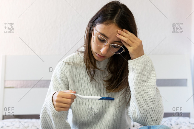 Young unhappy female with modern plastic pregnancy test with positive results