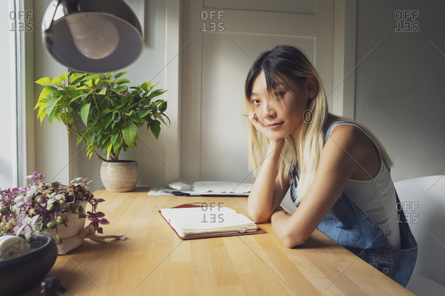 Side view of pensive Asian female sitting at table with diary and leaning on hand while looking at camera