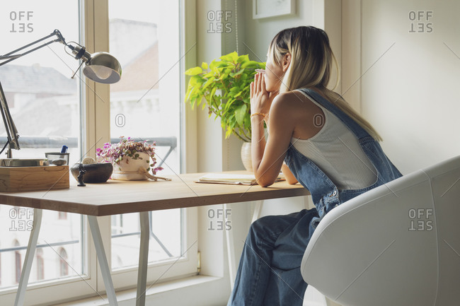 Side view of sad female leaning on hands and sitting at table at home while contemplating and looking away in frustration