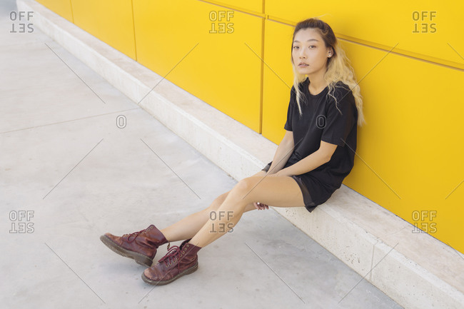 Full body side view of Asian teen female hipster in casual wear and boots sitting near yellow wall on city street
