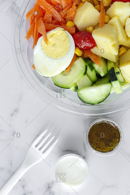 From above of various delicious vegetables and boiled egg placed in plastic container for takeaway food