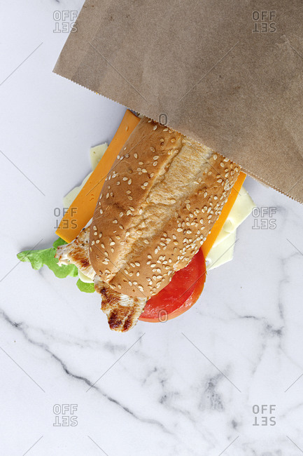 From above of yummy fresh sandwich with cheese and vegetables placed on table in takeaway paper bag
