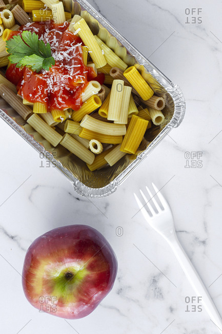 From above of delicious macaroni with ketchup and cheese placed in container for takeaway food on table with plastic fork and apple