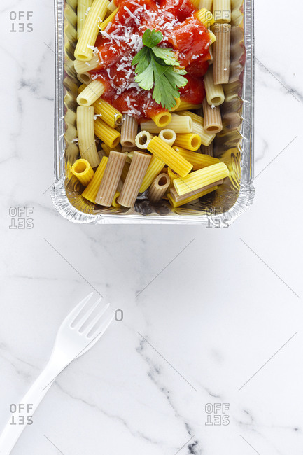 From above of delicious macaroni with ketchup and cheese placed in container for takeaway food on table with plastic fork