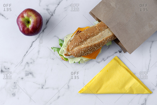 Top view of tasty nutritious sandwich in takeaway paper bag placed on marble table with fresh red apple