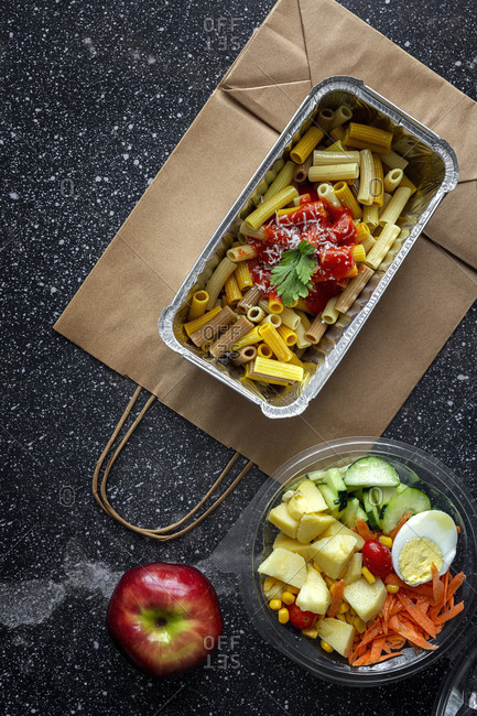 Top view composition with delicious pasta in foil box placed near salad bowl and fresh apple on table with paper bag prepared for takeaway lunch