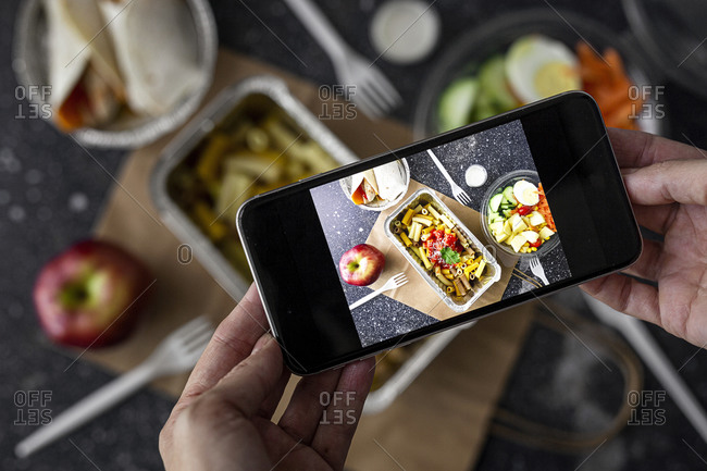 From above of crop unrecognizable blogger taking picture of takeaway food prepared for lunch while using smartphone