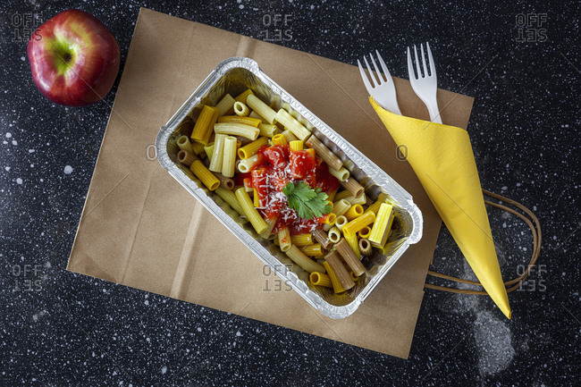 From above of delicious macaroni with ketchup and cheese placed in container for takeaway food on table with apple