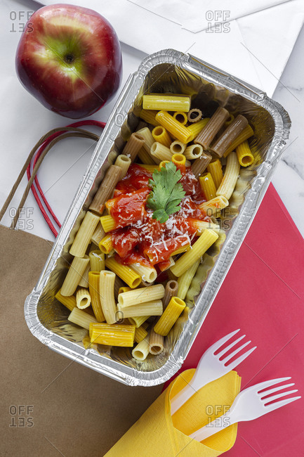Top view of foil box with delicious pasta with tomato sauce placed near fresh red apple on table with disposable forks and paper bags representing healthy takeaway food concept