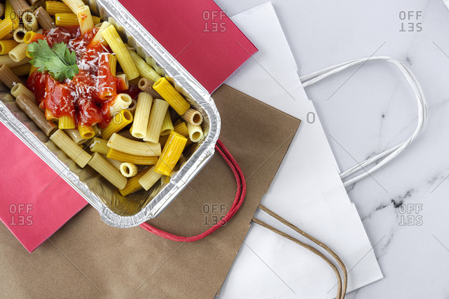 From above of delicious macaroni with ketchup and cheese placed in container for takeaway food on table