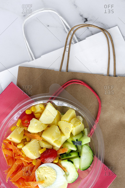 Top view of delicious salad with various vegetables and boiled egg in plastic bowl placed with paper bags on table for takeaway healthy food delivery concept