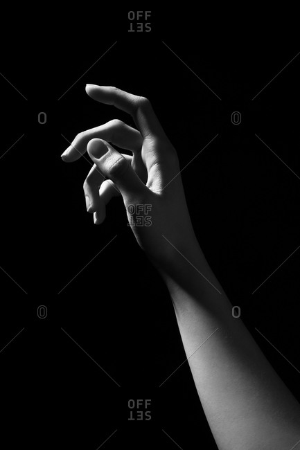 Black and white of crop anonymous female with slim arm on dark background in studio reaching towards light