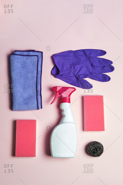 Top view of latex gloves and spray detergent arranged on pink and blue background with sponges and rag for cleaning concept