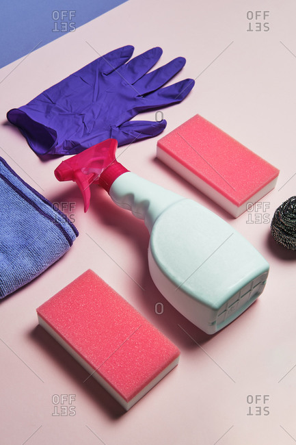 Top view of latex gloves and spray detergent arranged on pink background with sponges and rag for cleaning concept