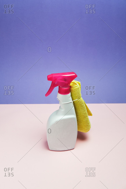 High angle of plastic bottle of window cleaner and rag placed on purple background in studio