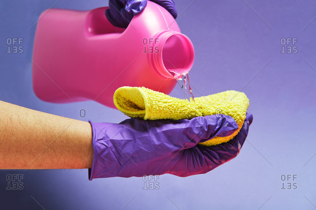 Crop anonymous person with plastic bottle pouring liquid detergent in a rag in studio