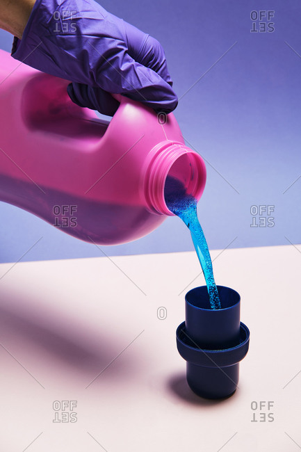 Crop anonymous person with plastic bottle pouring liquid detergent in cap placed on table in studio