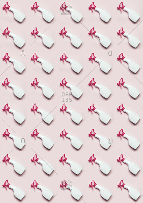 Top view of plastic bottles with window cleaner placed in even rows on pink background