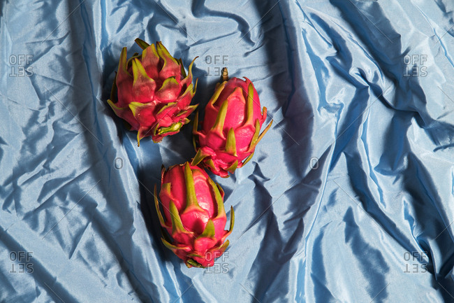 From above of whole fresh pitaya fruits arranged on blue wrinkled cloth in studio