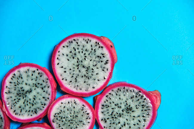 Top view of full frame background of round pieces of sweet juicy Pitaya fruit placed on blue background in studio