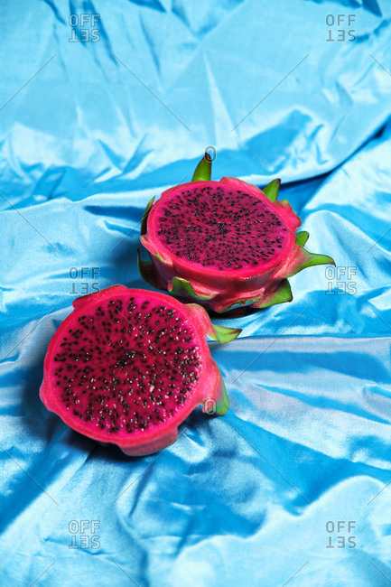 High angle of halves of delicious pitaya fruit placed on wrinkled blue cloth in studio