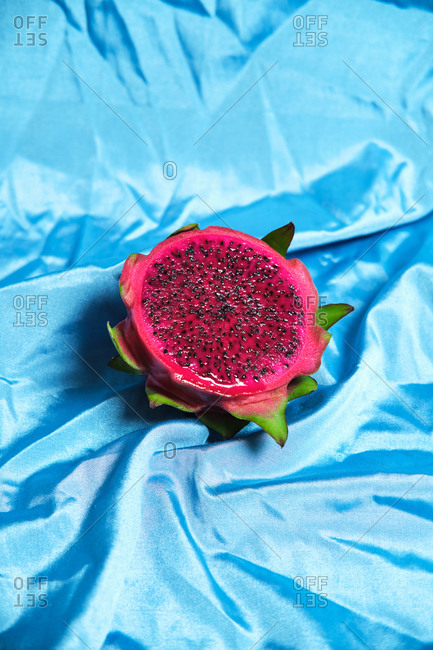 High angle of halve of delicious pitaya fruit placed on wrinkled blue cloth in studio