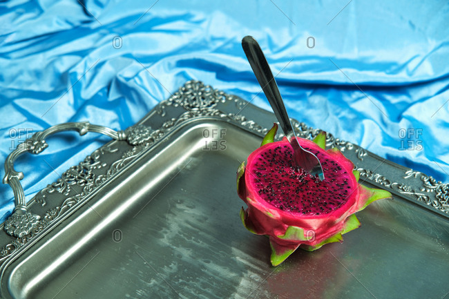 High angle of half of fresh juicy dragon fruit with fork placed on metal tray on blue wrinkled textile in studio