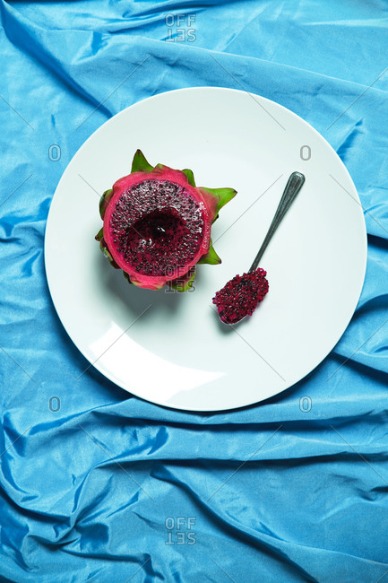 High angle of half of fresh juicy dragon fruit with spoon placed on metal tray on blue wrinkled textile in studio