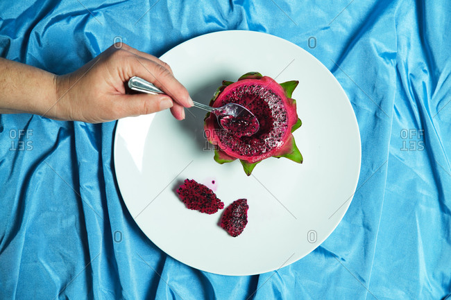 Top view of crop anonymous person with spoon eating delicious dragon fruit placed on plate on blue background in studio