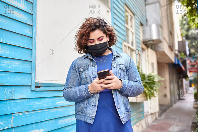 Plus size female wearing protective mask standing in narrow street near residential building and browsing smartphone during COVID 19 epidemic in city