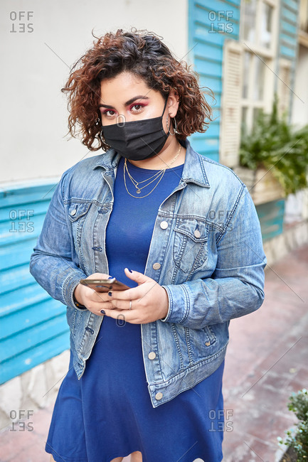 Plus size female wearing protective mask standing in narrow street near residential building and browsing smartphone during COVID 19 epidemic in city looking at camera